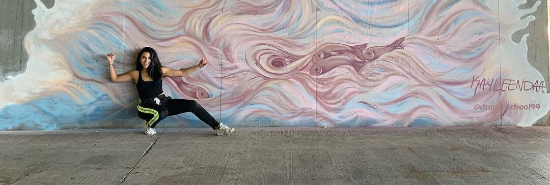 Picture of Kayleen in front of a mural she created