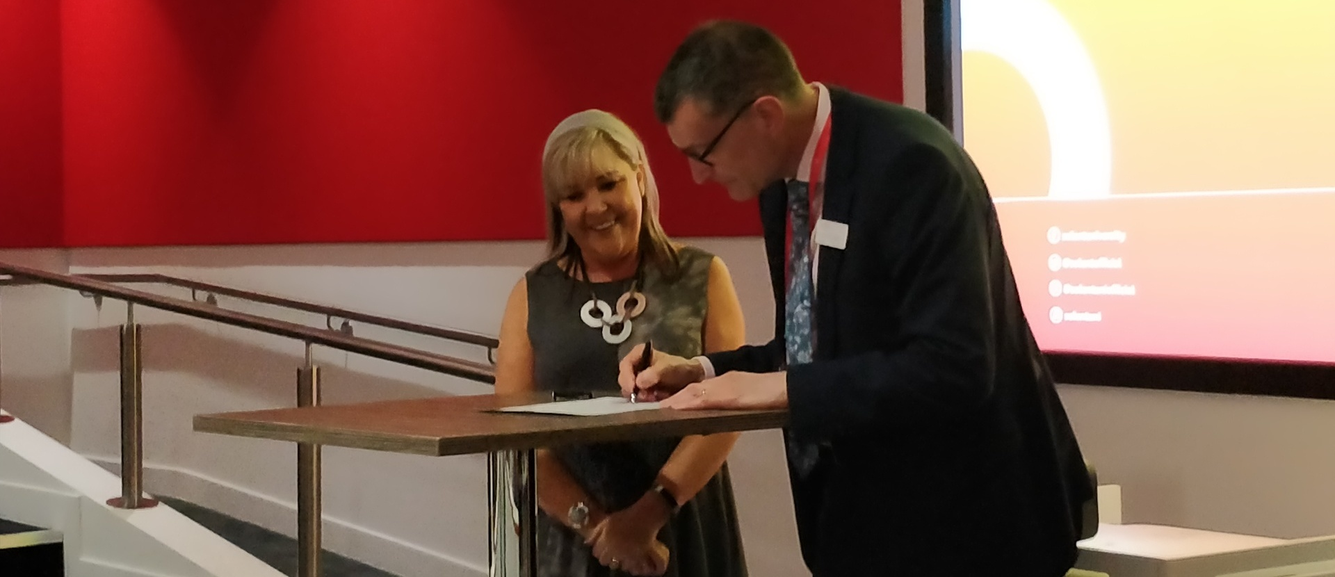 Diane Celella and Professor Graham Baldwin signing to show the launch of the SBID Centre of Excellence