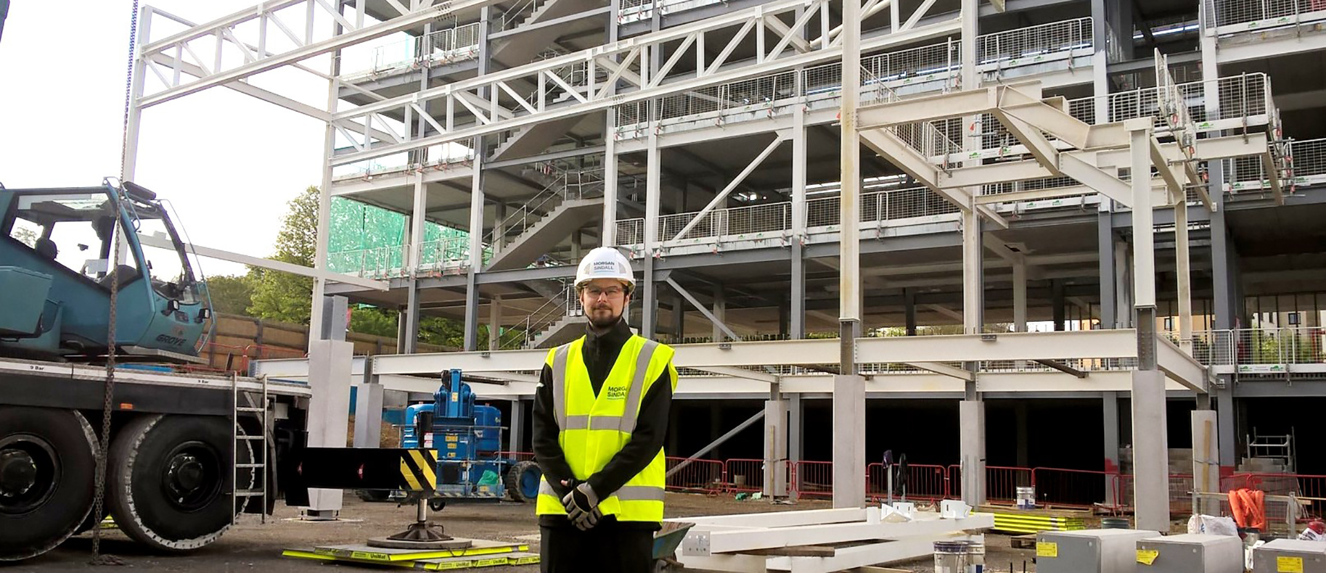 Graduate Harry White in front of the Sports Complex in construction