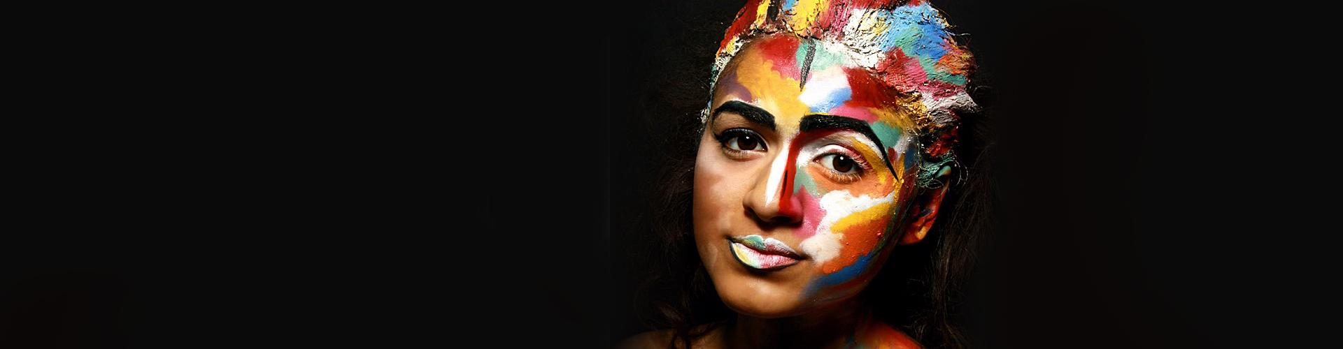 A woman covered in multi-coloured paint.