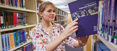 A criminology student taking a book from a shelf in the library
