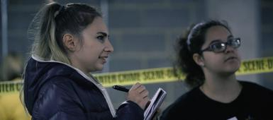 Two criminology students taking notes at a mock crime scene