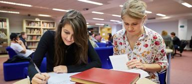 Two psychology students working on a project in the library